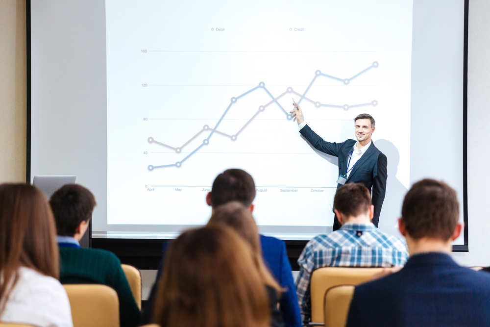 Smiling handsome speaker standing and explaining graphs on business conference in meeting hall.jpeg